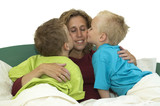 Mother and two sons lying happy in bed, kissing mommy. poster