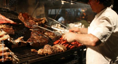Leinwanddruck Bild Argentinian chef cooking meat in the restaurant