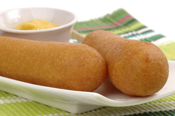 Golden corndogs on a plate with mustard.
