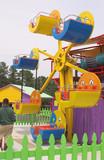 A kiddie ferris wheel at an amusement park. poster