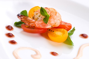 Closeup of spicy grilled shrimps and basil tomato salad served.
