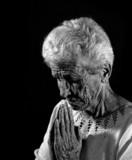 Senior Citizen in Deep Prayer in Monochrome poster