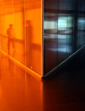 People reflected in angled orange corridor poster