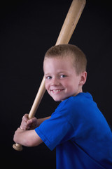 Cute little eight year old boy holding a baseball bat.