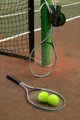Tennis court with balls and rackets in front of net