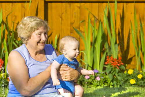 Grandmother holding happy grandson in the garden