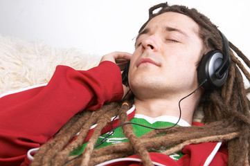 Young man sleeping on sofa listening to music