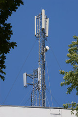 Two masts with cell antennas on a roof, against blue sky