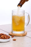 Pouring fresh cold beer into mug and salted almond . poster