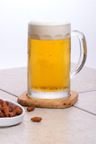 Mug of fresh cold beer with salted almond. poster