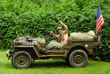 Man in military style in old fighting jeep