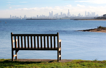 Park bench on a clifftop, overlooking a bay to city skyline