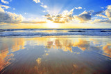 Fototapety Spectacular golden sunrise over ocean with beach in foreground