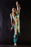 Dancer in Arabian costume does vertical splits poster