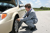 A businessman has a flat tire on the road. poster