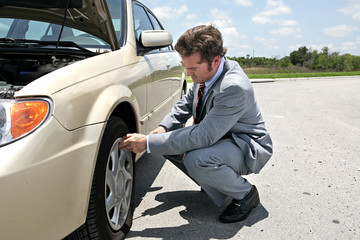 A businessman has a flat tire on the road.