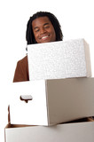 A smiling youg man carrying an armload of heavy boxes poster