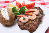 A steak and shrimp dinner over a plaid tablecloth poster