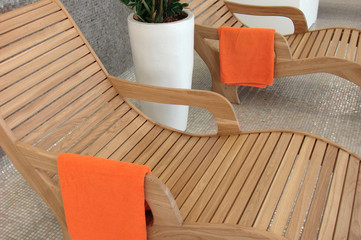 Two sunbeds with orange towels, plant between