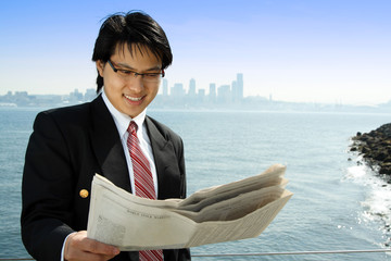 A businessman reading a financial newspaper on the beach