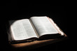 Old open bible lying on a wooden table in a beam of sunlight