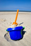 Orange plastic spade and blue bucket in the sandy seashore poster