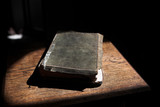 Leather covered old bible lying on a wooden table in a beam
