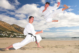 men with black belt practicing Karate on the beach