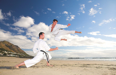 Young adult men with black belt practicing on the beach