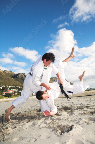 Men with black belt practicing fighting on the beach