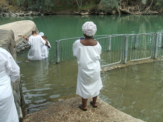 Religious people baptizing/wading in the water of Jordan river