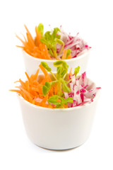 Carrot and radish salad in white bowl on white background