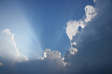 Sun projecting rays behind clouds in the blue sky