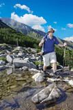 Hiker crossing a river in national park Pirin, Bulgaria poster