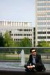 Geschäftsmann im Schneiderstiz vor Bürogebäuden