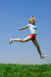 happy young woman jumping over green grass medow