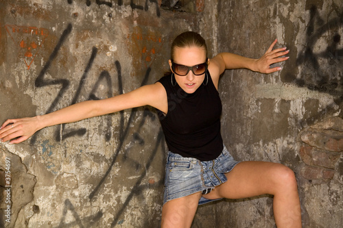 the young attractive woman standing at brick wall