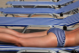 Legs of a girl in a stripped swimsuit on a stripped sun bed poster
