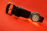 Silver watch with leather bracelet on a red background poster