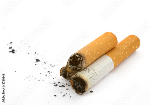 three cigarettes butts and ash against white background