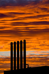 Backlit chimneys against fiery red dawning