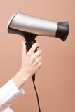Hair drier in hand isolated on beige background poster