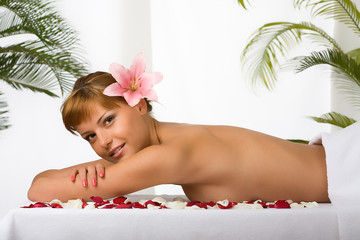 Preety lady with flower in her hair relaxing on the table