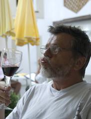 Mann verkostet Rotwein in einen Gastgarten