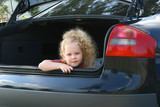 The beautiful girl sits in the open luggage carrier of the car. poster