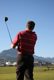 Young golfer following the ball against a blue sky poster