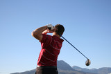 Golfer shot with a driver against blue sky poster