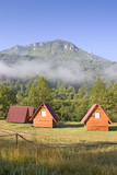 Misty morning in mountain camp. Small wooden houses in camp. poster