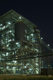 Industrial processing plant at night with lights poster