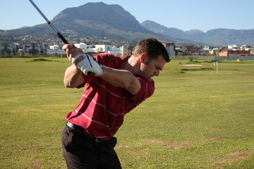 Young golfer practising on the driving range